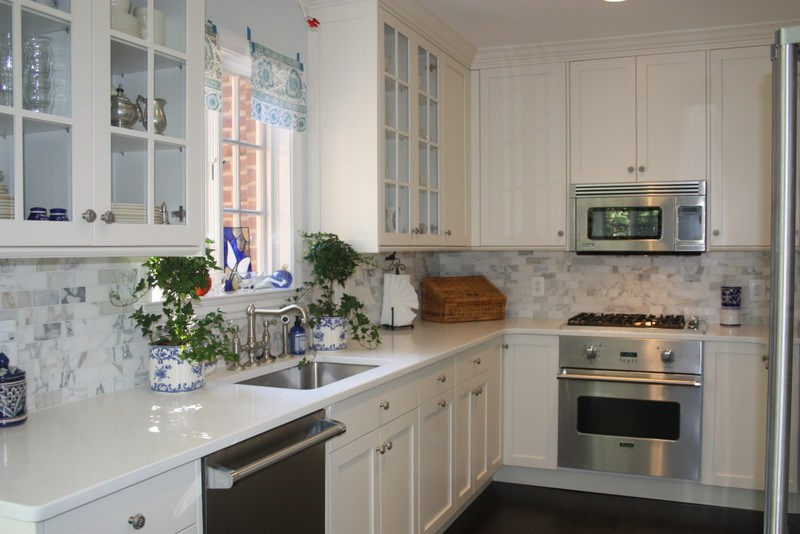 white kitchen cabinets and white countertops with stainless steel appliances to showcase how to budget for a kitchen remodel